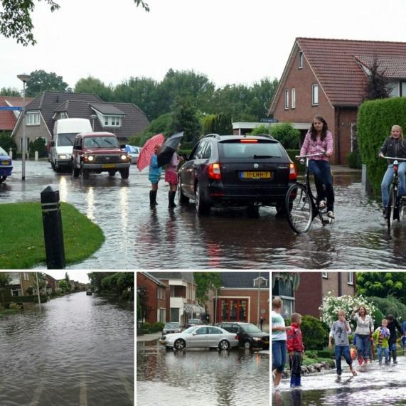 Foto van ondergelopen straat en mensen die met hun voeten in het water staan.
